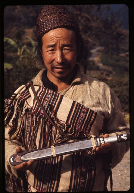 [Lepcha man in traditional bamboo hat and woven clothing holding knife in Singhik, Sikkim]