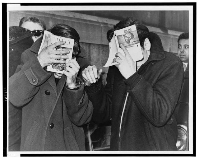 [Two Hunter College students covering their faces with books, at police headquarters after they were picked up on narcotics] / World Telegram & Sun photo by Herman Hiller.
