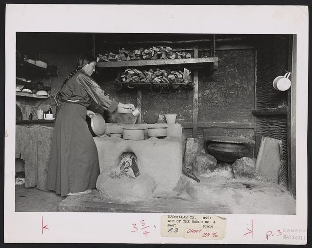 Typical hearth in Sikkim. Wood for fire heats top level where mother pours water to boil, wood dries on rack above. Container at right stores water / Alice S. Kandell.