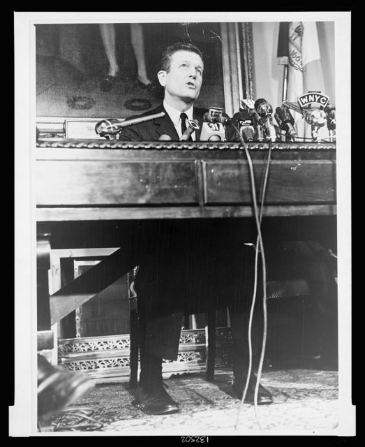 [Mayor John Lindsay, full-length portrait, seated behind desk and microphones, facing front, speaking at New York City Hall] / World Telegram & Sun photo by John Bottega.