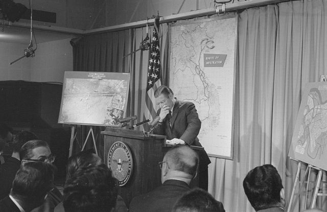 [Secretary of Defense, Robert McNamara standing at a podium in front of a map of Vietnam during a press conference] / MST.