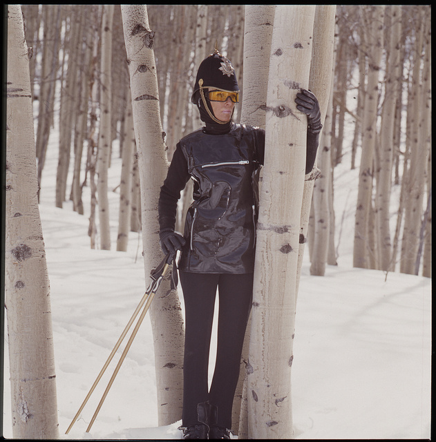 [Ann Bonfoey Taylor, full-length portrait,  standing next to aspen tree, in snow, wearing a ski outfit including a military dress helmet and goggles, Colorado]