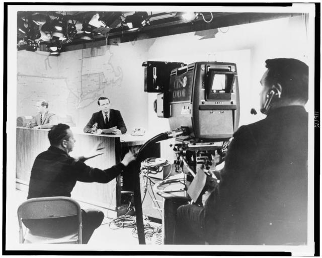 [Behind the camera during filming at a CBS news desk, map of New England in background] / World Journal Tribune photo by James Kavallines.