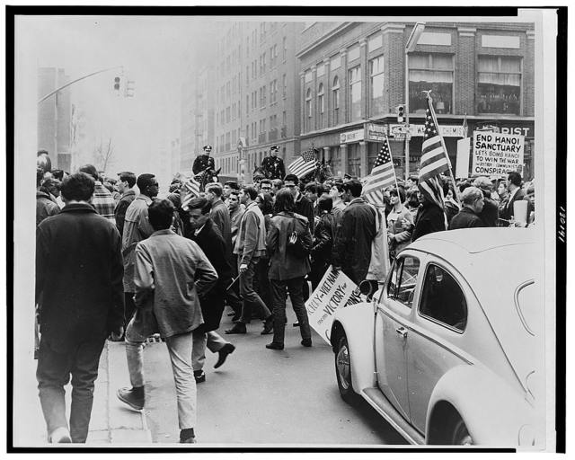 [Demonstrators, marching in a downtown area, with flags and placards in support of the war in Vietnam, police on horseback in background] / World Journal Tribune photo by Matthew Black.