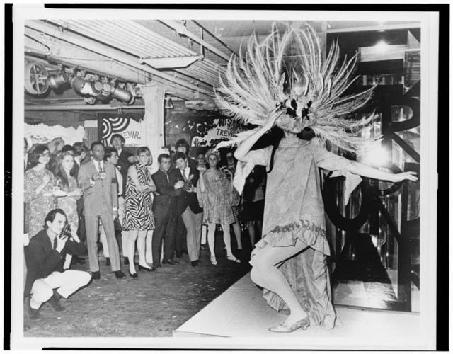 [Woman in costume, with large, feathered headdress, posing in front of audience, in club(?)] / World Telegram & Sun photo by James Kavallines.