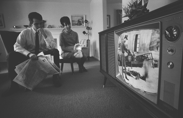 [A man and a woman watching a film footage of the Vietnam war on a television in their living room] / WKL.