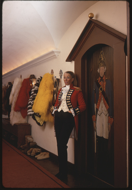 [Ann Bonfoey Taylor wearing a red military jacket, standing next to door painted with Hessian figure at her home in Vail, Colorado]