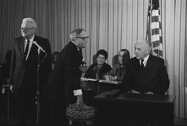 [Congressman Alexander Pirnie reaching into a container of draft numbers (center) as others look on, including retiring Selective Service Director Lt. General Lewis Blaine Hershey (left) and Deputy Director Col. Daniel O. Omer (right) at the Selective Service Headquarters during the nationwide draft lottery] / MST.