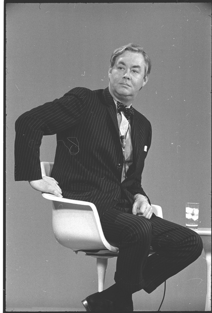 [Daniel Patrick Moynihan, three-quarter-length portrait, seated in plastic chair, facing front, at a two-way television conference between business leaders and the Nixon administration sponsored by the Chamber of Commerce]