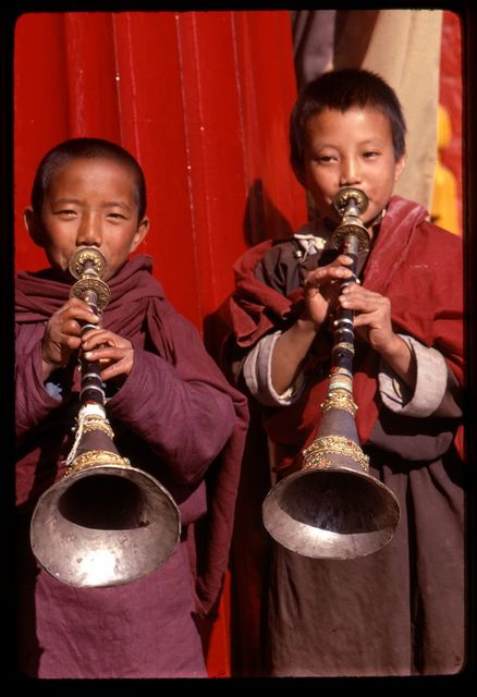 Lama boys with Gyalings (horns) of silver and goi[?] wood, Sikkim