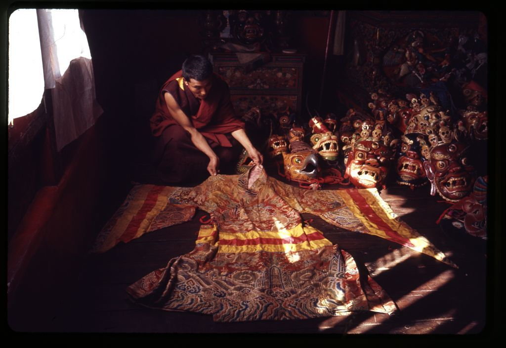 [Lama displaying brocaded robe and masks for the New Year's ceremony at the Tsuklakhang Main Temple (Palace Temple), Gangtok, Sikkim]