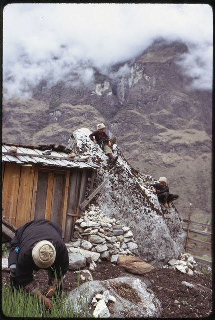 [Headman Pipon (front) near building with children, Lachung, Sikkim]