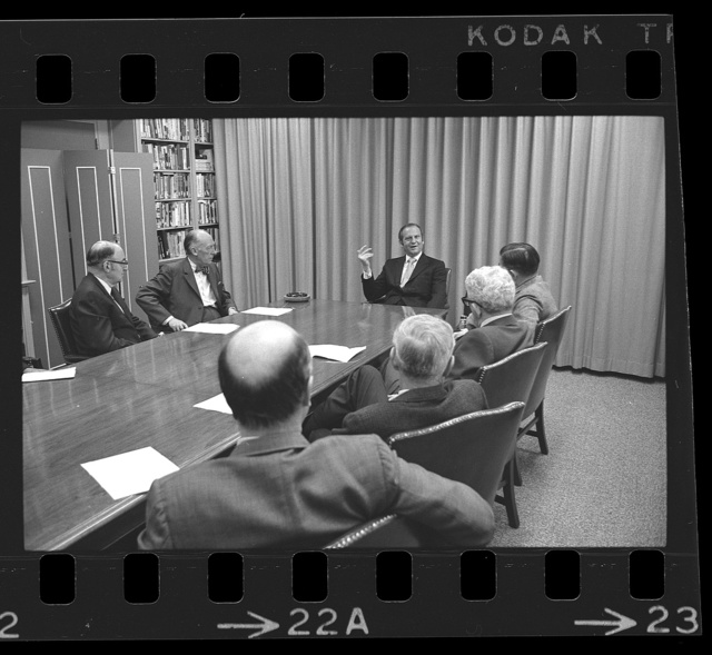 [Lee A. Iacocca, President of Ford Motor, seated at head of a table, with other men, during an interview] / TOH.