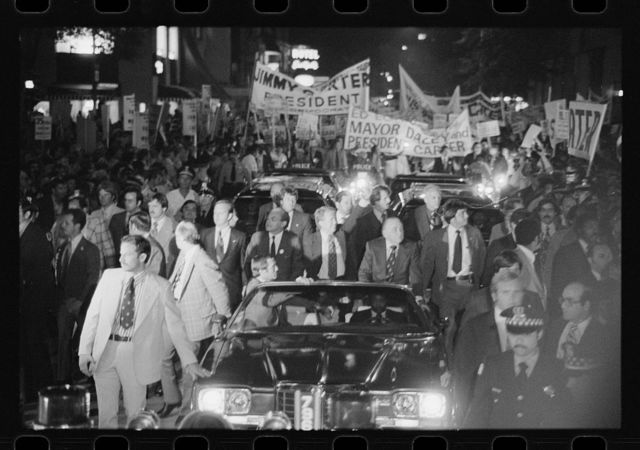 [Jimmy Carter and Mayor Richard J. Daley ride in a torchlight parade during a campaign stop in Chicago, Illinois]