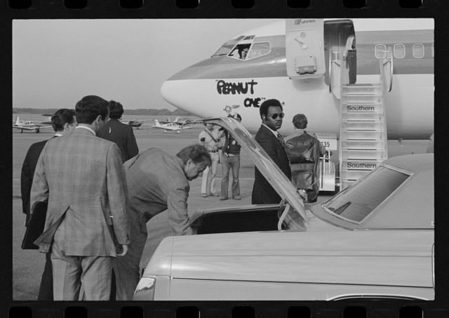 "[Jimmy Carter retrieving his luggage from a car before boarding ""Peanut One"" campaign airplane]"