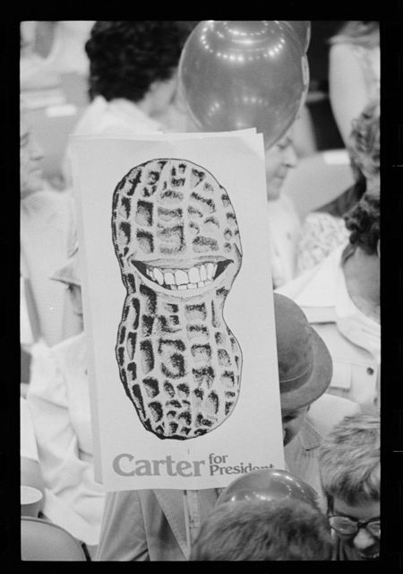 """[Jimmy Carter supporter holding """"Carter for President"""" sign showing a peanut shell with a toothy grin at the Democratic National Convention, New York City]"""