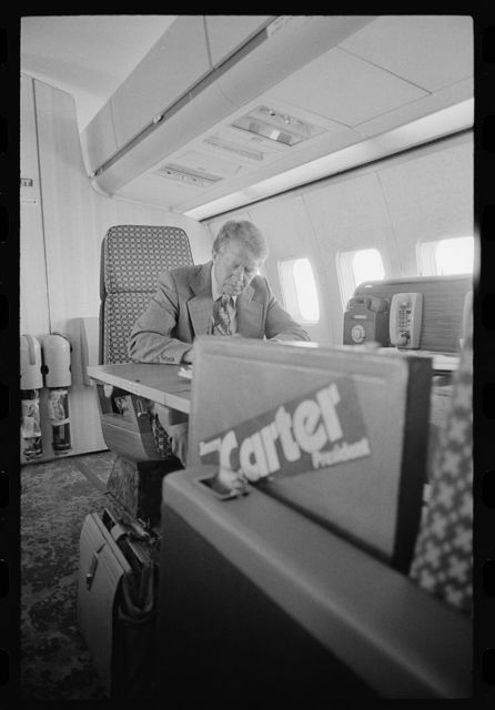 "[Jimmy Carter working aboard ""Peanut One"" campaign airplane]"