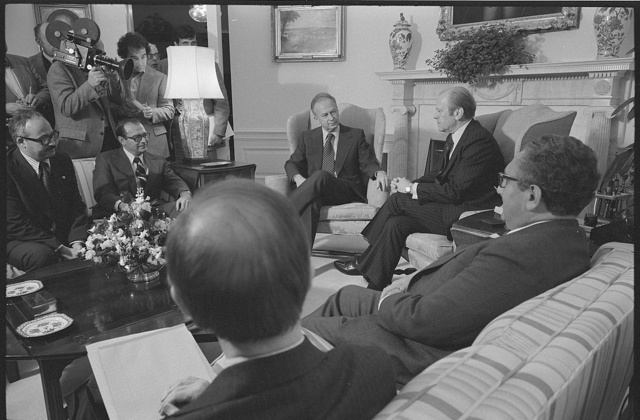 [President Gerald Ford (center) sitting in chair in front of fireplace, with Israeli Prime Minister Yitzhak Rabin (left) and others including Henry Kissinger (right), at the White House]