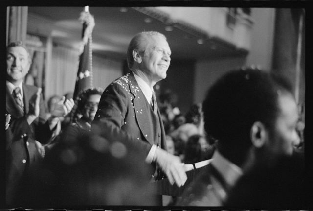 [President Gerald Ford, covered with confetti, smiles at crowd after his arrival in Philadelphia, Pennsylvania, for the 1st presidential debate with Jimmy Carter]