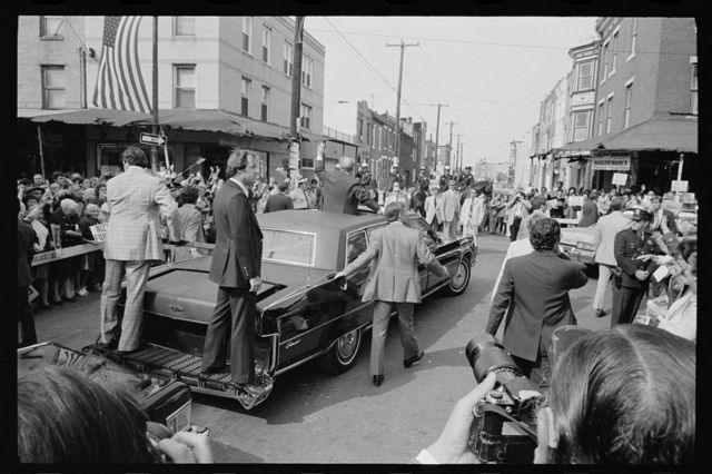 [President Gerald Ford, surrounded by security staff, waves to crowd from the sunroof of a car in Philadelphia, Pennsylvania]