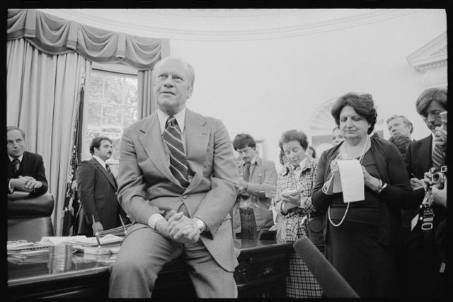 [President Gerald Ford talks with reporters, including Helen Thomas, as White House Chief of Staff Richard Cheney looks on, during a press conference at the White House, Washington, D.C.]