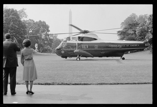 [First Lady Rosalynn Carter and unidentified man wave goodbye to President Jimmy Carter as he departs via helicopter from the White House lawn, Washington, D.C.]