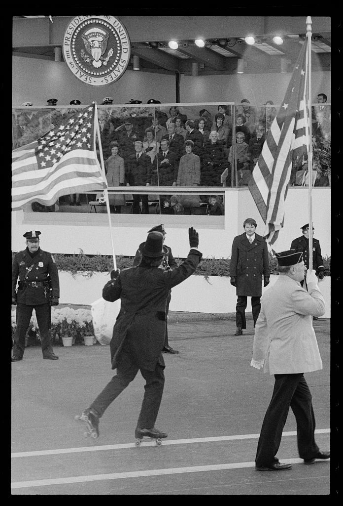 [Flag-waving, tuxedo-clad roller skater passes by reviewing stand for the inauguration of Jimmy Carter to President, Washington, D.C.]