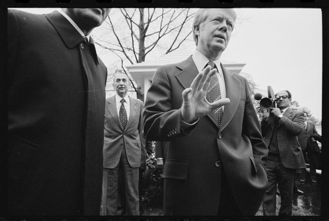 [President Jimmy Carter and Egyptian President Anwar Sadat surrounded by the media at the White House, Washington, D.C.]