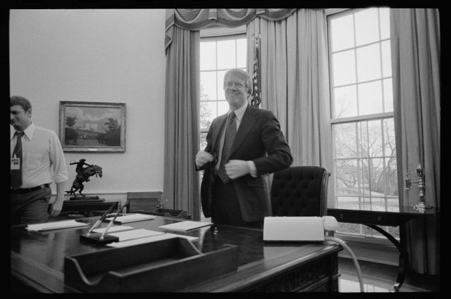 [President Jimmy Carter standing behind his desk in the Oval Office of the White House, Washington, D.C.]