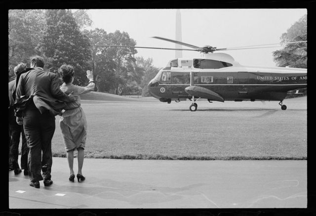 [Turning helicopter blades blow a strong wind on First Lady Rosalynn Carter and unidentified men as they wave goodbye to President Jimmy Carter departing from the White House lawn, Washington, D.C.]