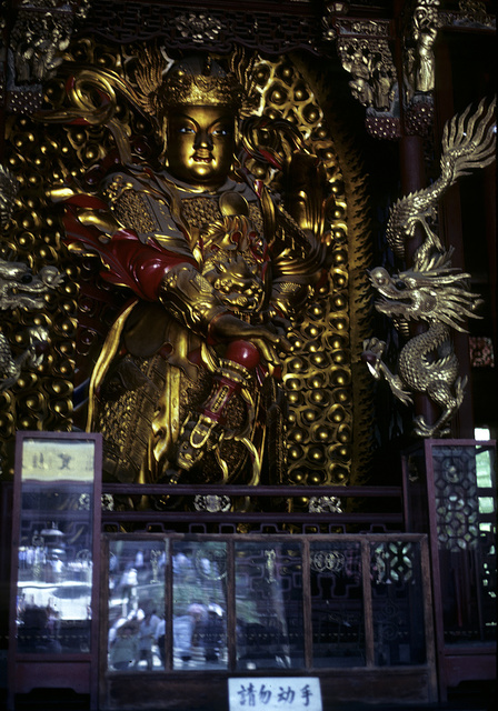 [Brass or golden guard, standing, with right hand on hilt of sword, with dragons on right and left, at a Buddhist temple in China]