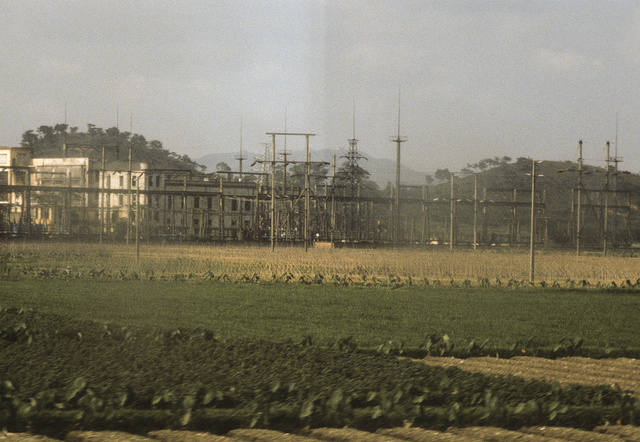 [Electrical lines and/or power station separating croplands from buildings, in China]