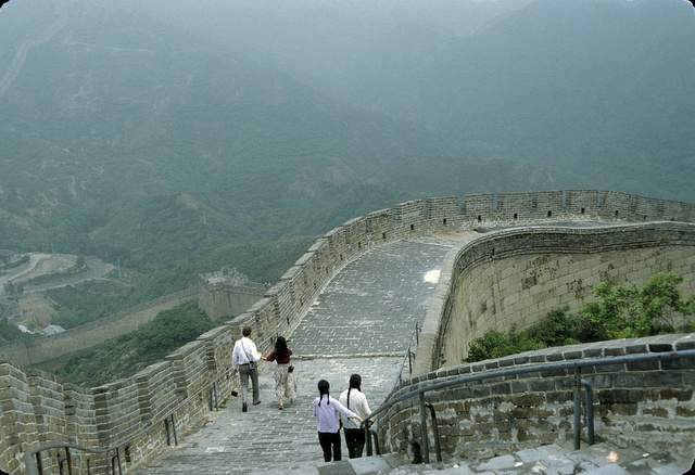 [Four sightseers walking on the Great Wall of China as it descends from the mountaintop toward the valley on the left]