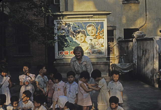 "[Jean E. Norwood with many young children, with a ""Welcome"" poster on a wall in the background, in Guangzhou, China]"