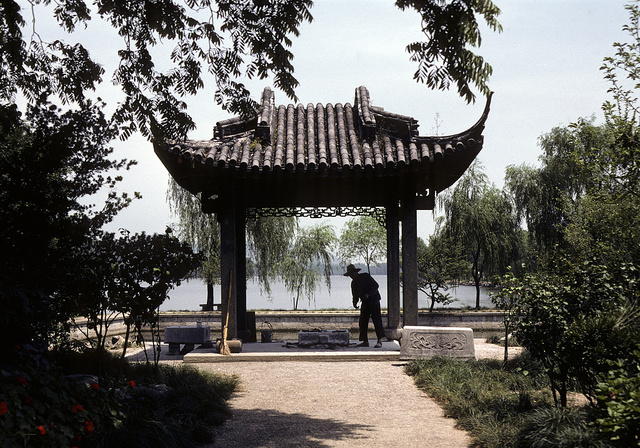[Maintenance worker standing at a temple gate, with gardens in the foreground and a large body of water in the background, in China]