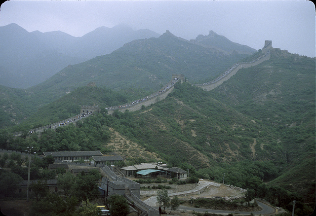 [Many sightseers walking on a section of the Great Wall of China, with buildings along the wall in the foreground and mountains in the background]