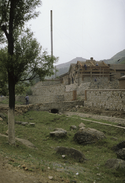 """[Putting new roof on a stone building that serves as a """"barracks"""", with the Great Wall of China in the background]"""