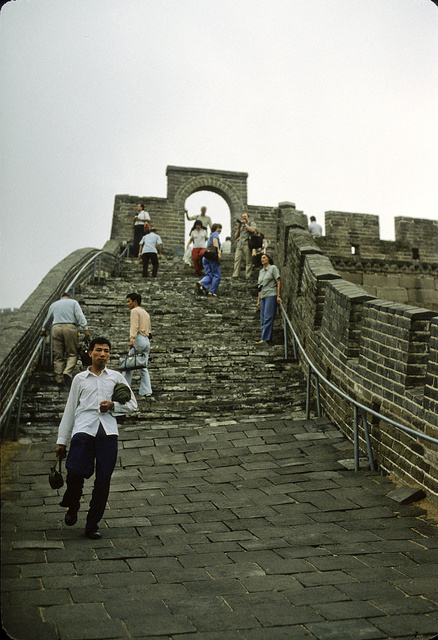 [Sightseers walking on a section of the Great Wall of China, showing the texture of the paving stones]