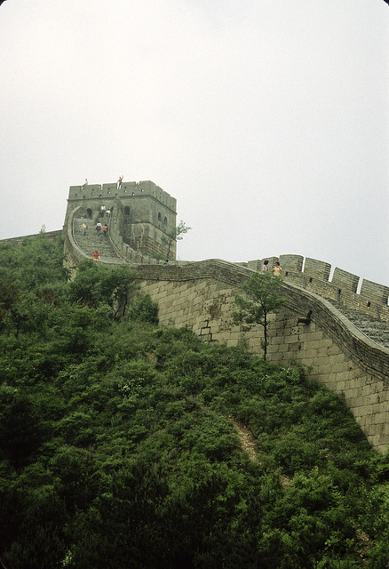 [Sightseers walking on a steep section of the Great Wall of China, with guard tower or blockhouse at the top of a hill]