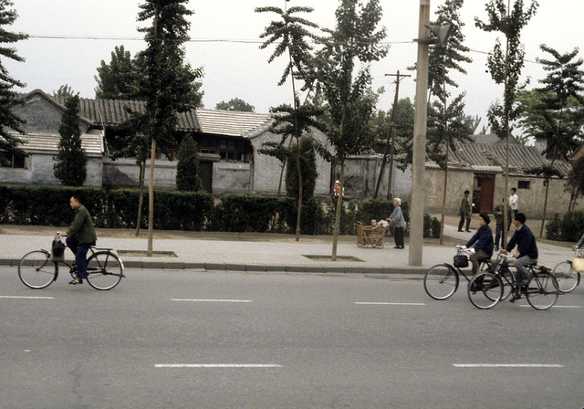 [Street scene with people riding bicycles and a woman pushing a baby stroller in Beijing, China]