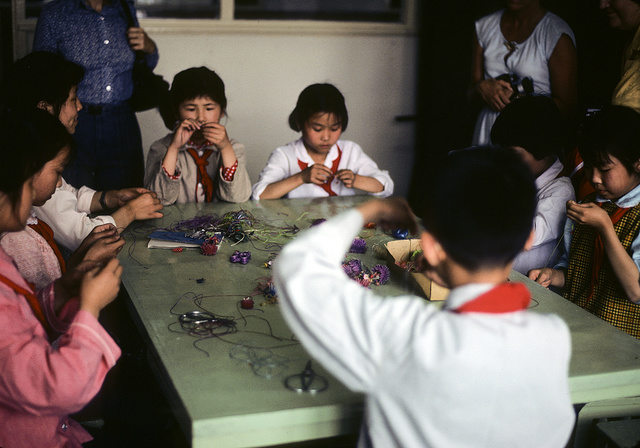 [Young children sitting around a table, making beadwork necklaces or bracelets, at the Children's Palace, Shanghai, China]