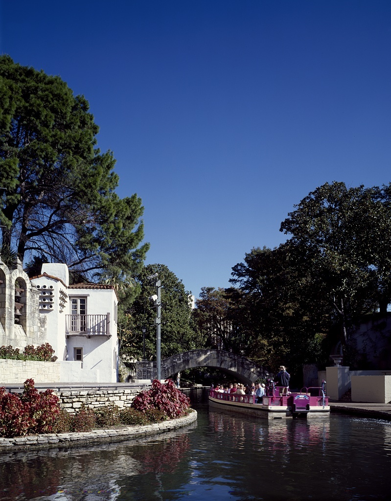 A tourist barge rounds the bend of the San Antonio River in San Antonio's River Walk, the leading tourist attraction in Texas