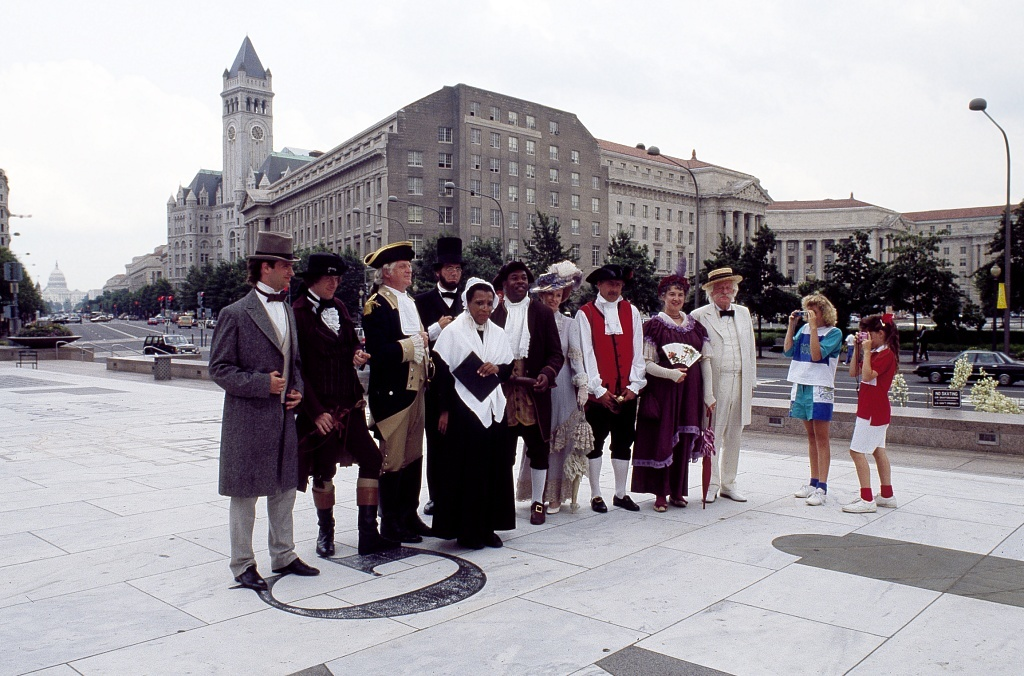 [Actors impersonating various historical figures, including Mark Twain and Abraham Lincoln, pose on Pennsylvania Avenue in Washington, D.C.]
