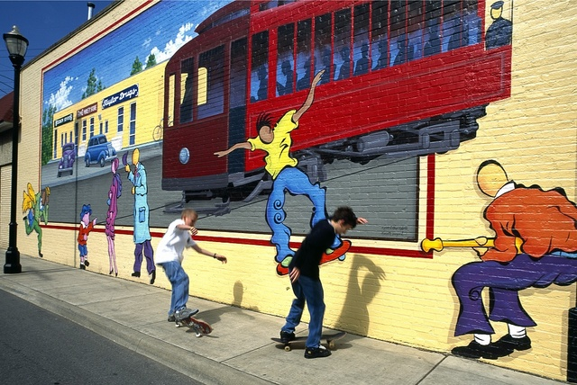 Actual skateboarders mimic those on a street mural, Louisville, Kentucky
