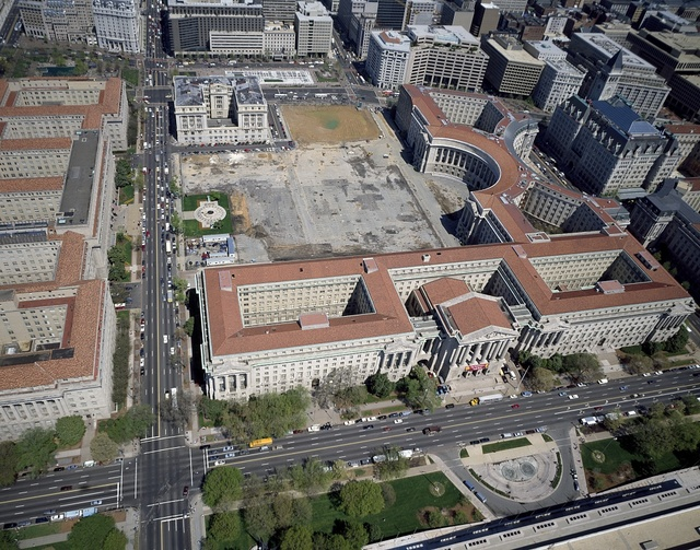 Aerial view in which the Federal Triange of federal government buildings is prominent, before the Ronald Reagan Building was built. Washington, D.C.