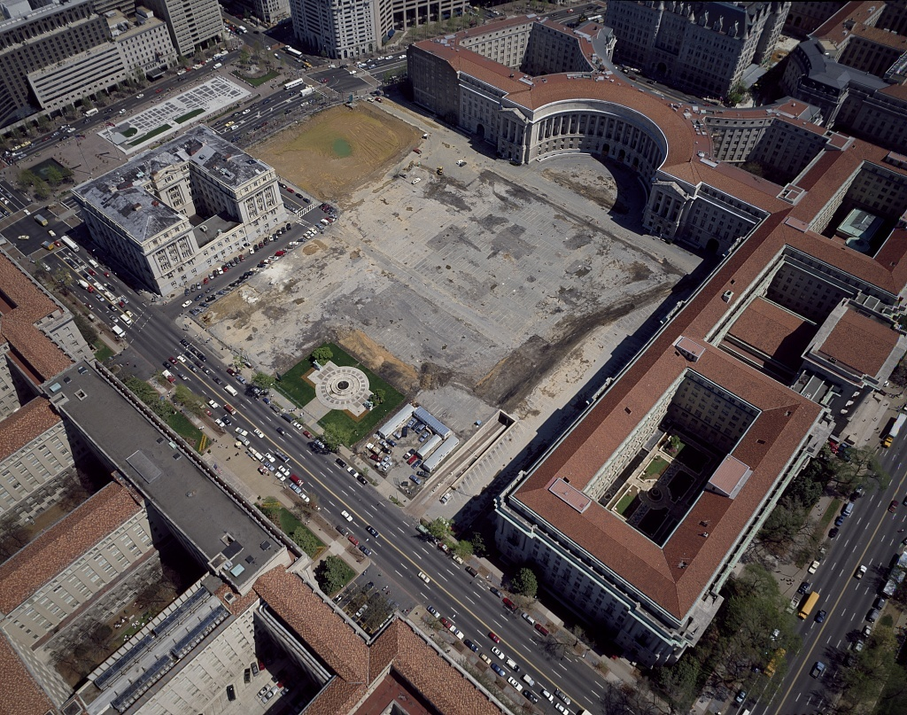"""Aerial view of Washington, D.C.  The red-roofed building with the notch is the Ariel Rios Post Office Department Building. The gray building next to it is the John A. Wilson Building, or """"District Building,"""" headquarters of the D.C. government"""