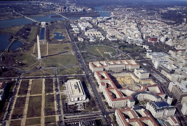 """Aerial view with a focus on the red-roofed federal buildings of the """"Federal Triangle,"""" Washington, D.C"""