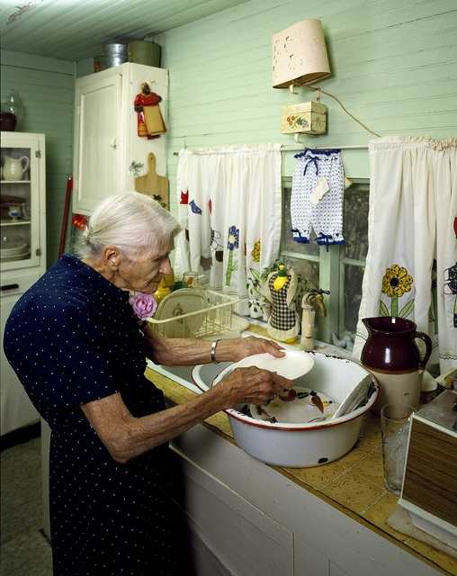 Elderly woman washing dishes in her cabin, Madison, North Carolina