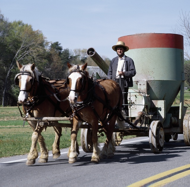Equipment being rolled down a country road road by Amish man, Lancaster, Pennsylvania