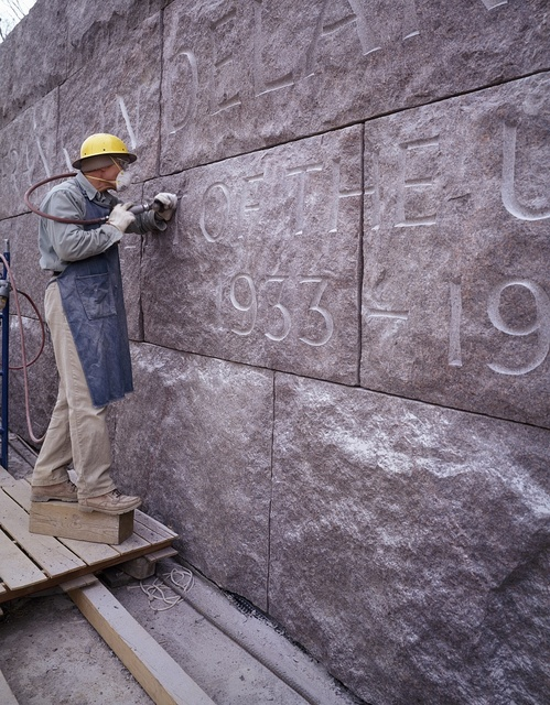 Etching words on stone at the building of the FDR Memorial in Washington, D.C.